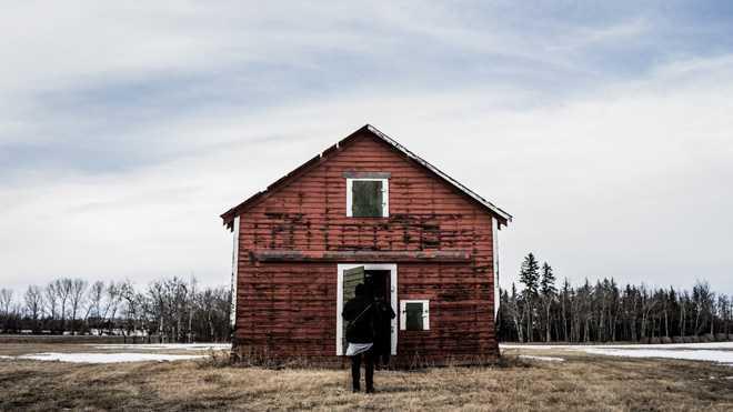 Человек стоит перед входом в дом