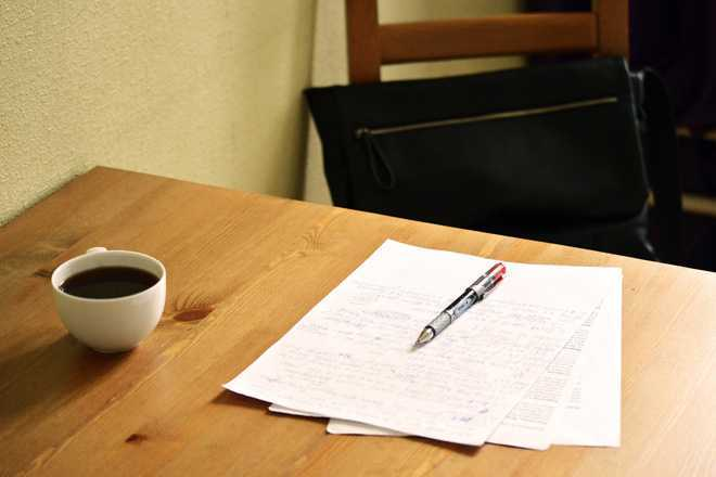 На столе стоит чашка чая, лист бумаги и ручка