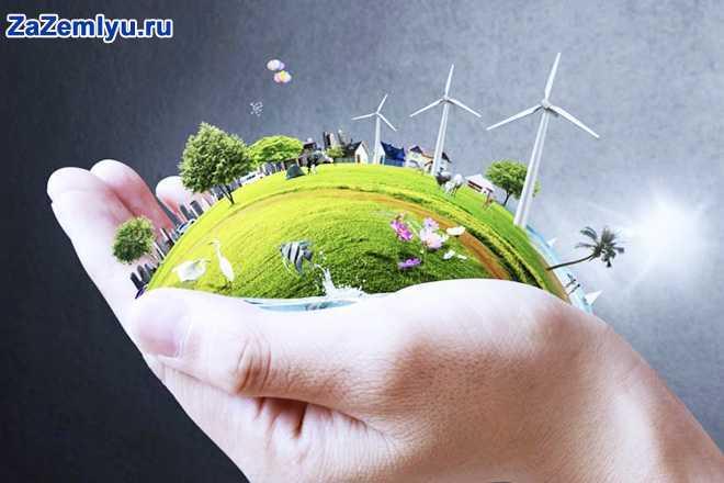 В руке человека кусочек земли с постройками