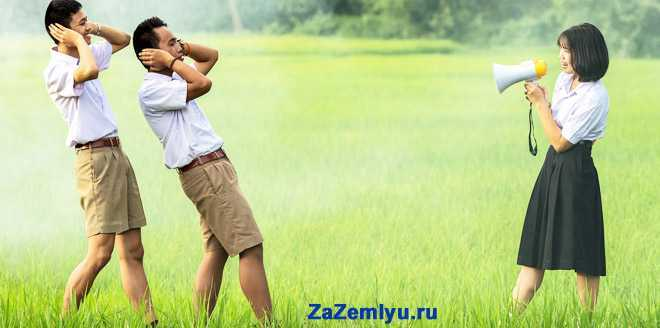 Девушка кричит из рупора на двух мужчин в поле