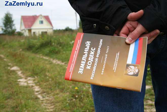 Мужчина подходит к дому, в руке держит земельный кодекс РФ