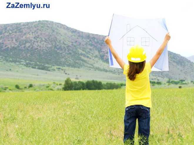Девочка в костюме строителя раскрыла карту на природе