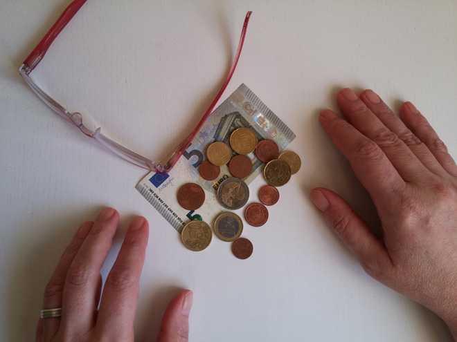 Человек считает деньги, на столе лежат очки