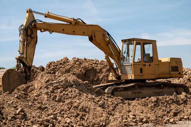 Строительная техника разравнивает песок