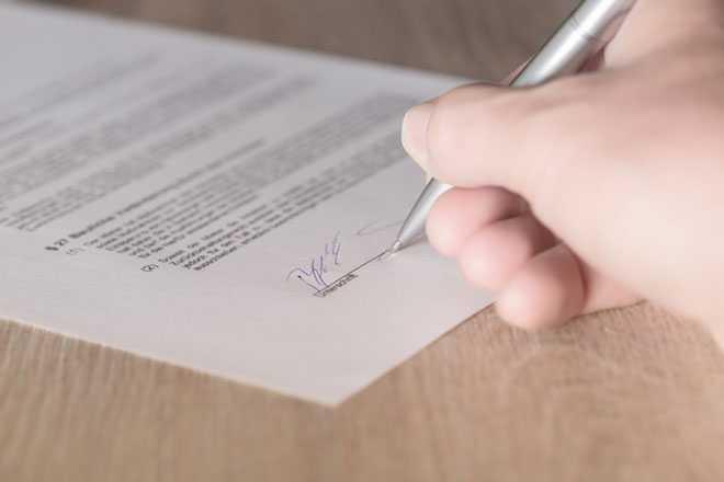 Мужчина ставит подпись в документе