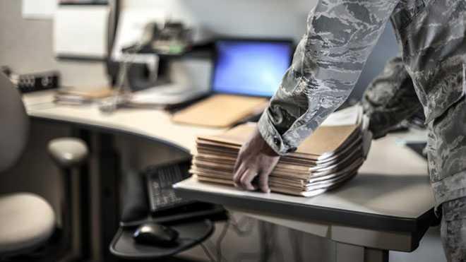 Мужчина кладет папку с документами на письменный стол