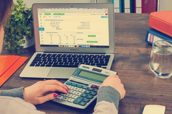 Девушка считает на калькуляторе, рядом стоит ноутбук