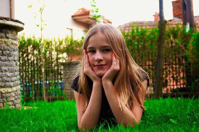 Девочка лежит на зеленом газоне