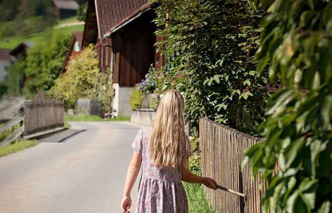 Девушка гуляет в деревне вдоль дороги