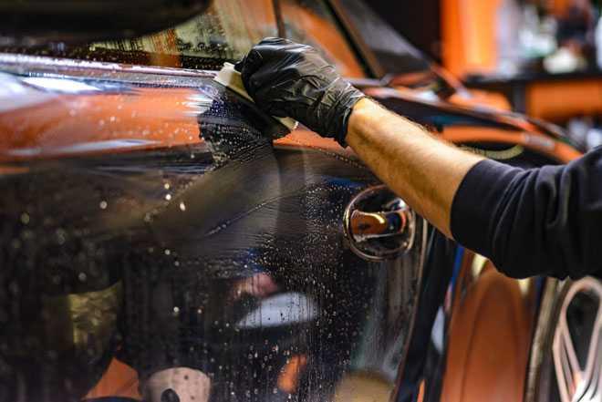 Автомеханик ремонтирует автомобиль в гараже