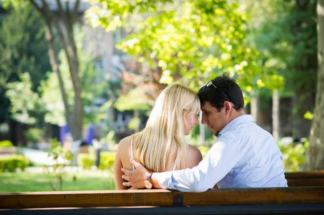 Молодая пара на скамейке в парке