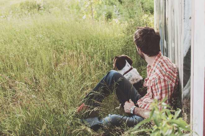 Мужчина с собакой сидит рядом с забором
