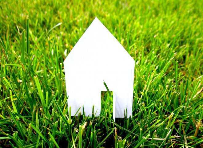 Бумажный домик на зеленой траве